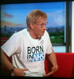 Comedian Dr Phil Hammond wears a Made by Young People 'Born in the NHS' t-shirt